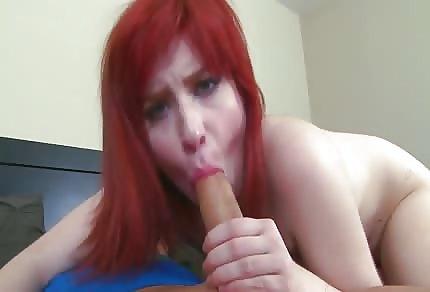 La calda ragazza con capelli rossi succhia la mazza